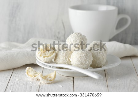White whole and broken coconut candy balls in plate and cup on rustic wooden background. White food styling. - stock photo