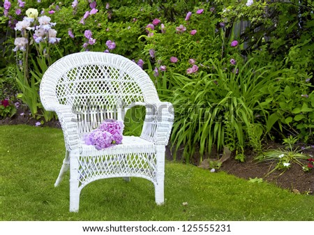 White wicker chair in the summer garden.
