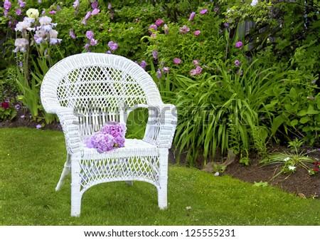White wicker chair in the summer garden. - stock photo