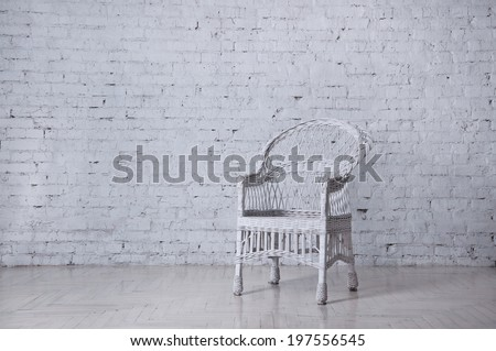 White wicker chair standing in an empty room in front of a brick wall on light parquet floor. Natural light from the window, reflection on the floor. Copy space - stock photo
