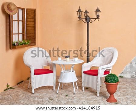 White wicker furniture Rattan European internal courtyard. Street light. - stock photo