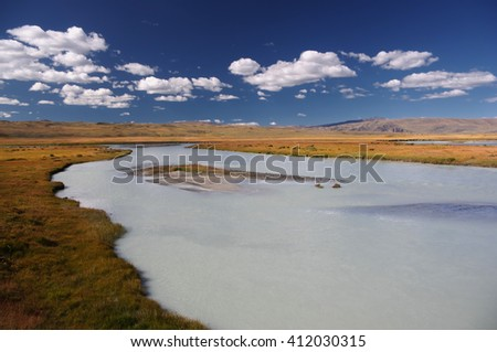 White wide river on a background of rocky hills under white clouds and blue sky, Plateau Ukok, Altai mountains, Siberia, Russia - stock photo