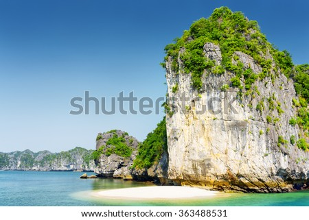 White wild beach on uninhabited tropical island in the Halong Bay (Descending Dragon Bay) at the Gulf of Tonkin of the South China Sea, Vietnam. Beautiful landscape formed by karst towers. - stock photo