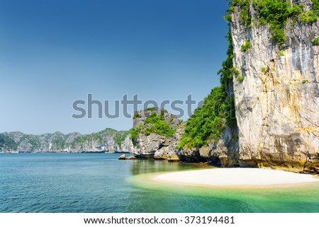 White wild beach on uninhabited tropical island in the Halong Bay (Descending Dragon Bay) at the Gulf of Tonkin of the South China Sea, Vietnam. Scenic landscape formed by karst towers. - stock photo