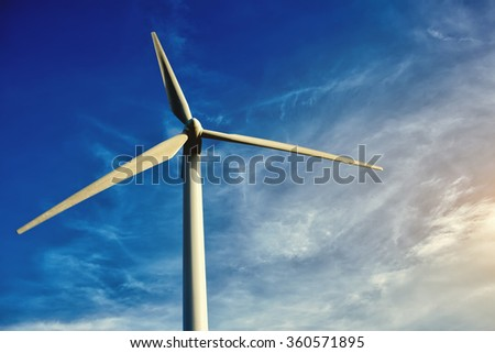 White wind turbine against blue cloudy sky at day, electric turbine with sky on background, alternative and renewable energy resources, windmill located outside the city  - stock photo
