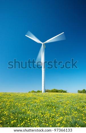 White wind turbine electric power generator under blue sky - stock photo