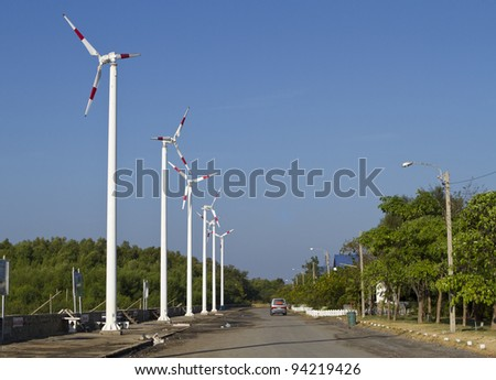 White wind turbine generating electricity on blue sky. - stock photo