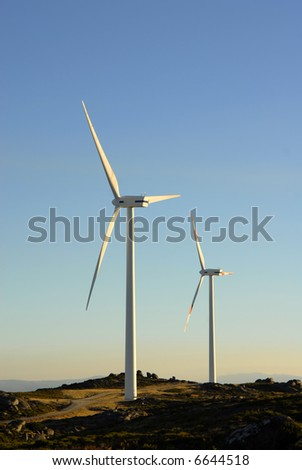 white wind turbine in the top of the mountain