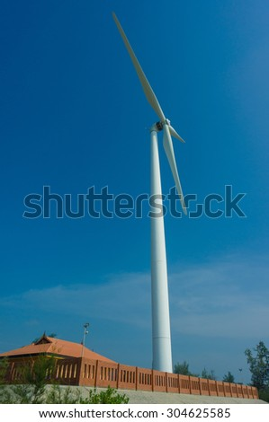 White wind turbines generating electricity on blue sky