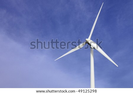 white windmill with blue and cloudy sky
