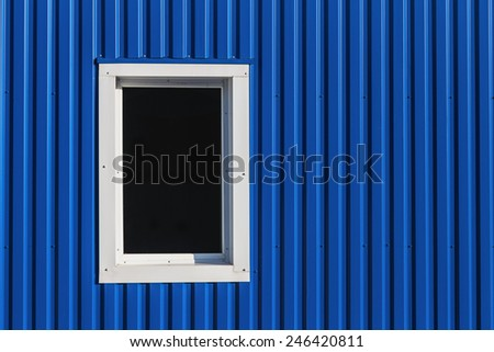 White window in blue color metal siding wall - stock photo