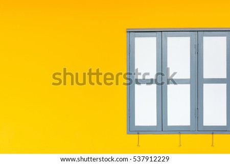 White window on yellow wall background.