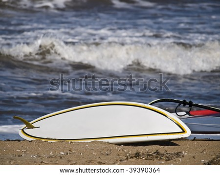 White Windsurf boat on the sand of a beach, with the waves of the shore on the background - stock photo