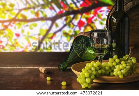 White wine and grapes on a wooden table with of natural.