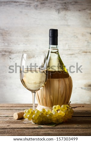 White wine and grapes on vintage wooden table - stock photo