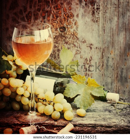 White wine and grapes/ Wine and grapes in vintage setting with corks on wooden table - stock photo