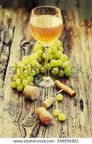 White wine and grapes/ Wine and grapes in vintage setting with corks on wooden table