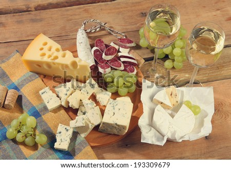 white wine and snacks on wooden table - stock photo