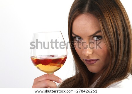white wine and strawberries in a crystal glass - a beautiful young smiling brunette with large breasts in a white sexy silk peignoir - stock photo