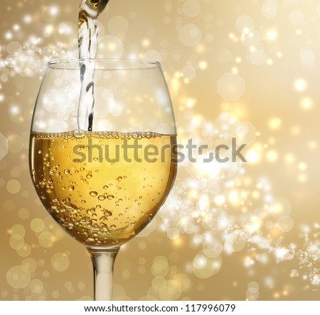 White wine being poured into a wine glass on shiny gold background - stock photo