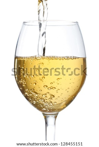 White wine being poured into a wine glass on white background - stock photo