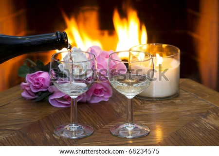 White wine being poured into one of two glasses in front of a fireplace. - stock photo