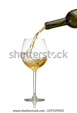 White wine being poured into wine glass on white background - stock photo