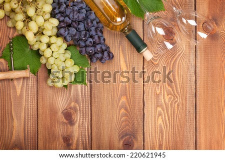 White wine bottle and bunch of grapes on wooden table background with copy space - stock photo