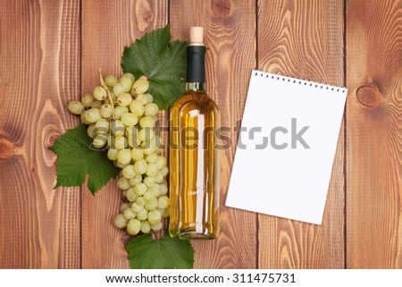 White wine bottle and bunch of white grapes on wooden table background with notepad for copy space - stock photo