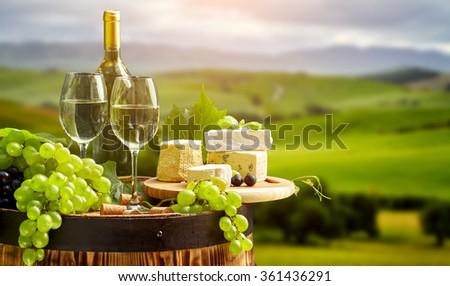 White wine bottle and wine glass on wodden barrel. Beautiful Tuscany background - stock photo