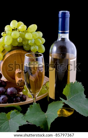 White wine bottle, glass and cask with grapes over black - stock photo