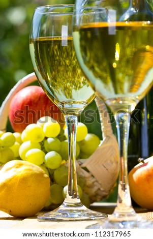 White wine - bottle, glasses, grapes, apples and pear - stock photo