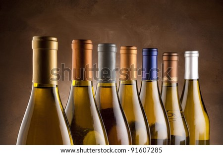 White wine bottles lined up in a row - stock photo