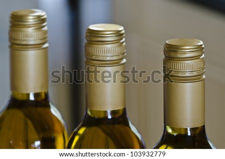 White wine bottles with stelvin caps and close focus on nearest bottle - stock photo