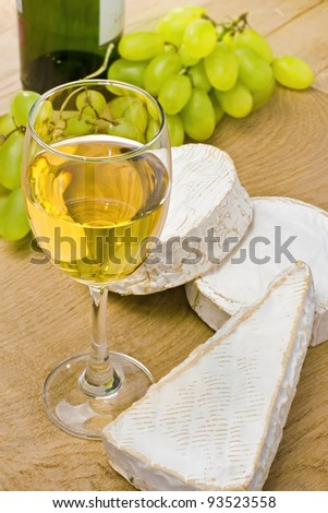 White wine, brie, caembert and grape on the wood surface - stock photo