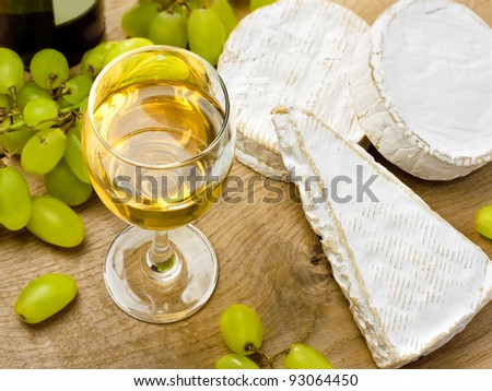 White wine, Brie, Camembert and grape on the wood surface - stock photo