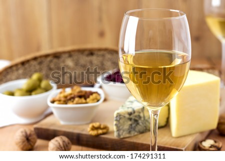 White Wine, cheese, nuts, olives, dried fruit, bread and garlic on wooden table - stock photo