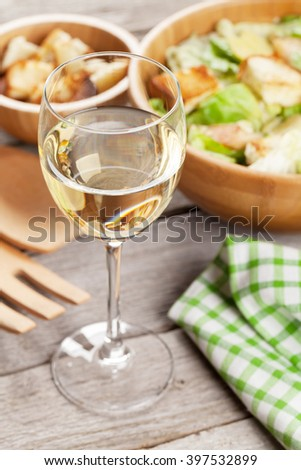 White wine glass and caesar salad on wooden table