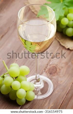 White wine glass and grapes on wooden table