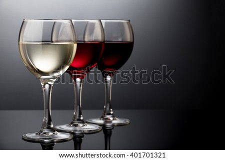 White wine glass, red wine glass and rosy wine glass isolated on black - stock photo