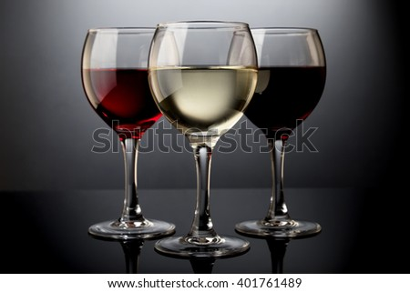 White wine glass, rosy wine glass, red wine glass isolated on black gradient - stock photo