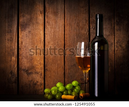 White wine, grapes, corkscrew, and bottle on wood background closeup - stock photo
