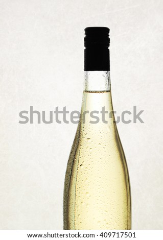 white wine in a bottle with no label, against a textured background - stock photo