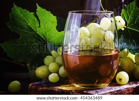 White wine in a glass, green grapes with leaves in a wine cellar, a vintage wooden background, selective focus - stock photo