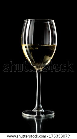 White wine in a glass on black background - stock photo