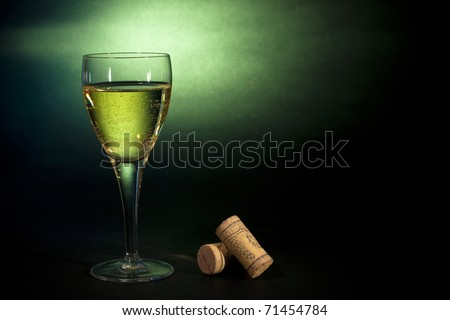 White wine in a glass, on black-green background. Art background - stock photo