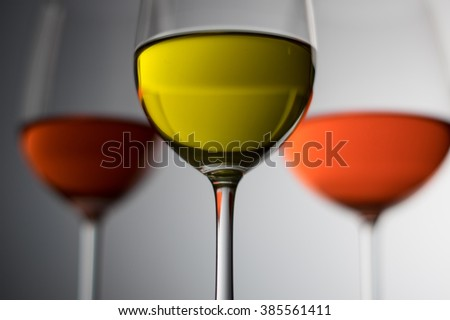 white wine in a glass  on red wine and red wine background / selective focus