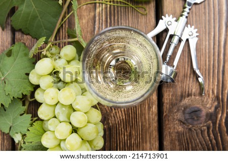 White Wine in a glass with fresh grapes (on wooden background) - stock photo
