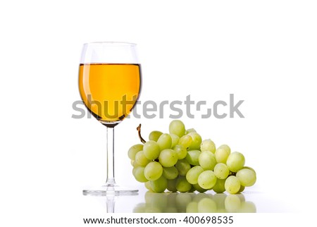 White wine in a glass with the grapes on white background