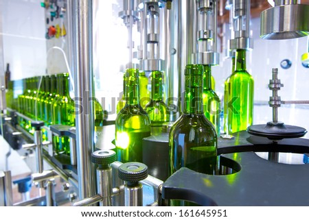 white wine in glass bottling machine at winery - stock photo